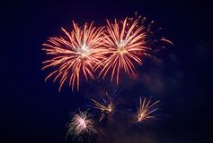 A few volleys of festive fireworks in the night sky, red-yellow royalty free stock photo