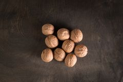 Few whole walnuts sprinkled on an old dark wooden table. Few walnuts sprinkled on the old dark wooden table Royalty Free Stock Photos