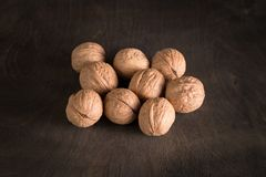 Few whole walnuts sprinkled on an old dark wooden table. Few walnuts sprinkled on the old dark wooden table Stock Photography
