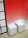 Few white seat, red wall, interior,. Few white seat (cube padded stool), red wallю new interior concept Royalty Free Stock Photos