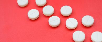A few white tablets lie on a bright red background surface. Background image on medical and pharmaceutical topics.  Royalty Free Stock Images
