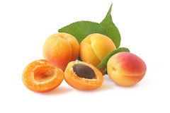 Few whole apricots and two hales with twig isolated on white Royalty Free Stock Photos