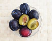 Few whole plums in the bowl with one halved plum on the top royalty free stock image