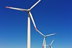 A few wind generator mills. In the blue sky Stock Photos