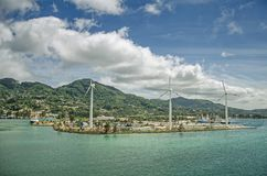 A few wind turbines on the island with green hills and big clouds Royalty Free Stock Images