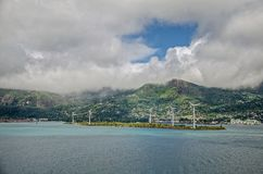 A few wind turbines on the island with green hills and big clouds Stock Photos