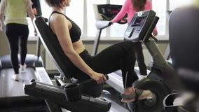 Few women are engaged in fitness on cardiovascular to maintain physical fitness. Several women in the fitness room are engaged in the training apparatus. Two stock video footage