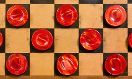 Red Pieces on a Checkerboard. A few wooden pearly red pieces on a checkerboard Royalty Free Stock Images