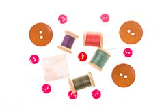 Few wooden spools of thread and colour buttons on white royalty free stock image