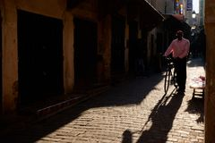 Fez, Μαρόκο - 7 Δεκεμβρίου 2018: Μαροκινός κύριος που περπατά κάτω από μια παλαιά οδό στο medina του Fez με ένα ποδήλατο στοκ εικόνα