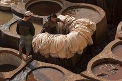 FEZ, MAROC - 20 FÉVRIER 2017 : Hommes travaillant dans les trous de peinture à la tannerie célèbre de Chouara en Médina de Fez Images libres de droits
