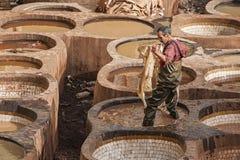 """FEZ MAROCKO †""""FEBRUARI 20, 2017: Man arbete på den berömda Chouara garveriet i medinaen av Fez, Marocko Arkivfoto"""