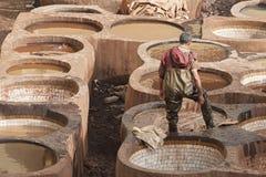 """FEZ MAROCKO †""""FEBRUARI 20, 2017: Man arbete på den berömda Chouara garveriet i medinaen av Fez, Marocko Arkivfoton"""
