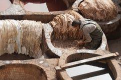 FEZ MAROCKO - FEBRUARI 20, 2017: Man som arbetar inom målarfärghålen på den berömda Chouara garveriet i medinaen av Fez Arkivbilder