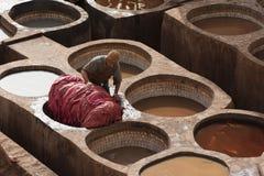 FEZ MAROCKO - FEBRUARI 20, 2017: Man som arbetar inom målarfärghålen på den berömda Chouara garveriet i medinaen av Fez Arkivfoton