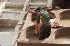 FEZ MAROCKO - FEBRUARI 20, 2017: Man som arbetar inom målarfärghålen på den berömda Chouara garveriet i medinaen av Fez Royaltyfri Bild