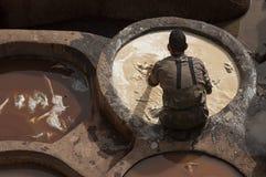 FEZ MAROCKO - FEBRUARI 20, 2017: Man som arbetar inom målarfärghålen på den berömda Chouara garveriet i medinaen av Fez Royaltyfria Bilder
