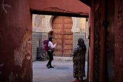 Fez, Marokko - 7. Dezember 2018: Kontrast zwischen einem Wanderertouristen und einer lokalen alten Dame im Medina von Fez lizenzfreie stockfotografie