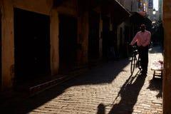 Fez, Marokko - 7. Dezember 2018: Marokkanischer Herr, der hinunter eine alte Straße im Medina von Fez mit einem Fahrrad geht stockbild