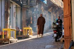 Fez, Marrocos - 7 de dezembro de 2018: Cavalheiro marroquino que anda abaixo de uma rua velha no medina do fez com uma luz de que imagem de stock royalty free