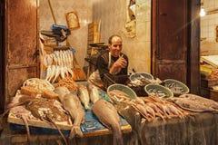 FEZ, MARROCOS - 18 DE FEVEREIRO DE 2017: Um homem não identificado que vende peixes e marisco em um mercado de rua no fez Imagem de Stock Royalty Free