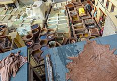 FEZ, MOROCCO – APRIL 10, 2016: Tanneries of Fez, Morocco, Afri. Ca. Workers working hard in a Africa Old tanks of the Fez`s tanneries with color paint for royalty free stock images