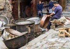 FEZ, Morocco, artisan man pounding copper pot in old Medina souk. FEZ, Morocco, May 24, 2014:Artisan man pounding copper pot in old Medina souk, Seffarine place Royalty Free Stock Photos