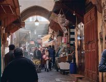 Fez, Morocco - December 07, 2018: Moroccan lady with her daughter walking through a passage of the fez medina with rays of light royalty free stock photos