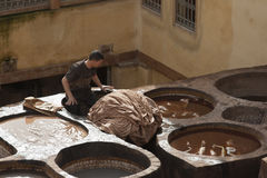 FEZ, MOROCCO - FEBRUARY 20, 2017: Man working within the paint holes at the famous Chouara Tannery in the medina of Fez. Royalty Free Stock Image