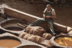 FEZ, MOROCCO - FEBRUARY 20, 2017: Man working within the paint holes at the famous Chouara Tannery in the medina of Fez. Royalty Free Stock Photography