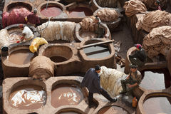FEZ, MOROCCO - FEBRUARY 20, 2017: Men working within the paint holes at the famous Chouara Tannery in the medina of Fez. Stock Photos