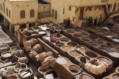 FEZ, MOROCCO - FEBRUARY 20, 2017: Men working within the paint holes at the famous Chouara Tannery in the medina of Fez. Royalty Free Stock Photos