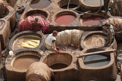 FEZ, MOROCCO - FEBRUARY 20, 2017: Men working within the paint holes at the famous Chouara Tannery in the medina of Fez. Stock Photo