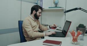 Ffice pracownik, siedzi przy jego biurka klapaniem na klawiaturze jego laptop, uśmiechniętą twarz i koncentrat zdjęcie wideo