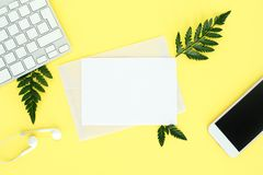 Fflatley en fondo amarillo con el teclado, el smartphone, los auriculares y las hojas del helecho, fotos de archivo libres de regalías