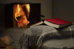 Öffnen Sie Buch durch Kamin. Stockbilder