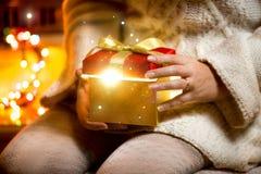 Öffnungsgeschenkbox der jungen Frau mit dem Licht, das aus sie herauskommt Stockfotografie