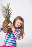 FHappy little girl holding a pineapple Royalty Free Stock Photo