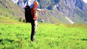 Hiking man walking on green mountain meadow with backpack. Summer sport and recreation concept. FHD Hiking man walking on green mountain meadow with backpack stock video