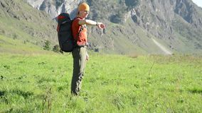 Hiking man walking on green mountain meadow with backpack. Summer sport and recreation concept. FHD Hiking man walking on green mountain meadow with backpack stock video footage
