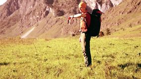Hiking man walking on green mountain meadow with backpack. Summer sport and recreation concept. FHD Hiking man walking on green mountain meadow with backpack stock footage