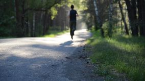 Sport man running at asphalt road. Rural city park. Green tree forest and sun rays on horizon. FHD sport man running at new asphalt road outdoor. Sunrise or stock footage