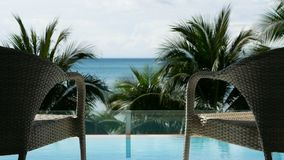 FHD. Zoom out of two relaxing vacation chair in front of swimming pool near the beach with coconut palm tree and sea view. At background. travel , vacation and stock video footage
