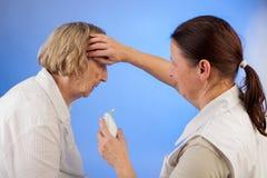 Fièvre de mesure d'infirmière à une femme agée Image stock
