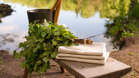 Fińscy lata sauna i krajobrazu przedmioty na ławce jeziorem Fotografia Royalty Free