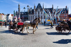 Fiaker with tourists in Grote Markt square, Bruges, Belgium Royalty Free Stock Photography