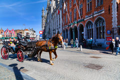 Fiaker with tourists in Grote Markt square, Bruges, Belgium Stock Photo