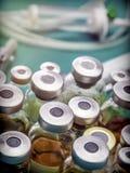 Fiale della dimensione differente accanto alle siringhe ad una tavola dell'ospedale, Fotografia Stock Libera da Diritti