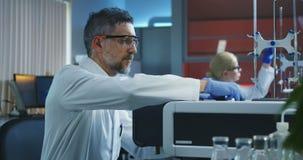 Fiale di caricamento dello scienziato in una macchina di prove video d archivio