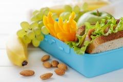 Fiambrera azul con el bocadillo, la manzana, el plátano y las nueces en la tabla de madera blanca Foto de archivo